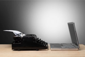 typewriter and computer sitting on desk